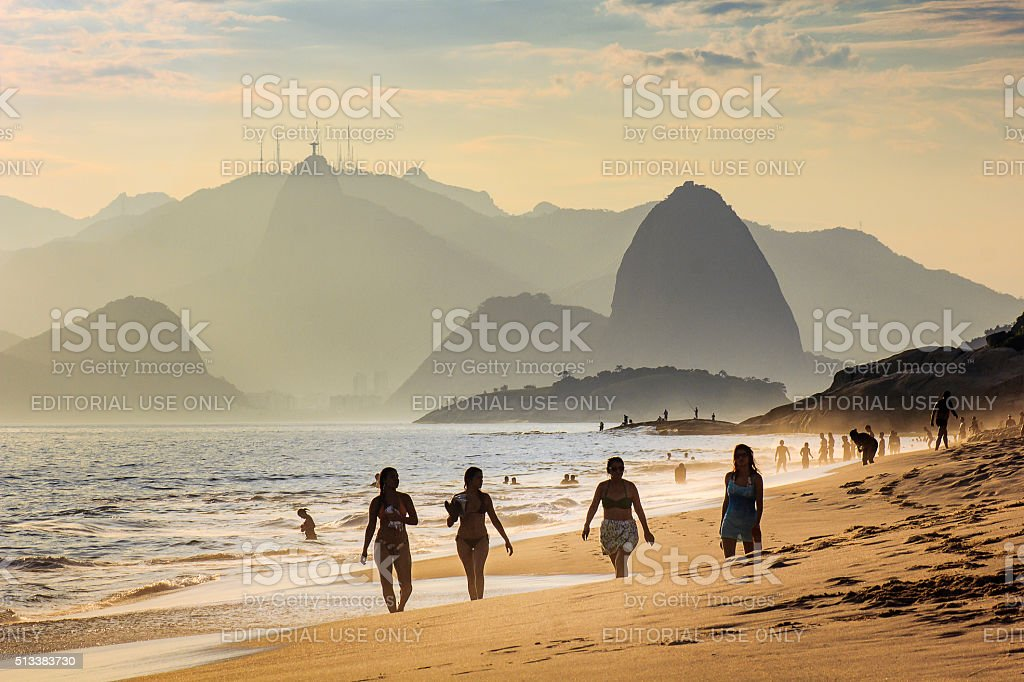 Four Girls Taking a Walk at the Beach by Sunset stock photo
