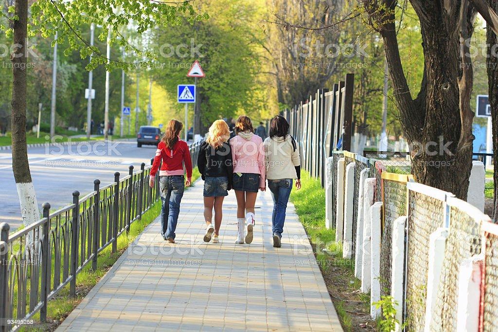Four girls walking along the street stock photo