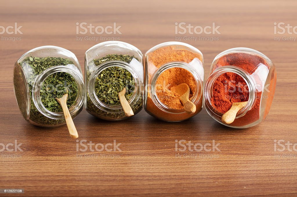Four glass jar with spices with wooden spoon stock photo