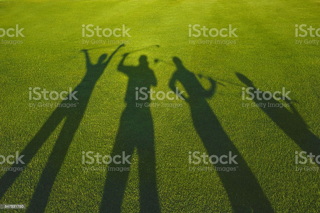 Four golfers silhouette on grass stock photo