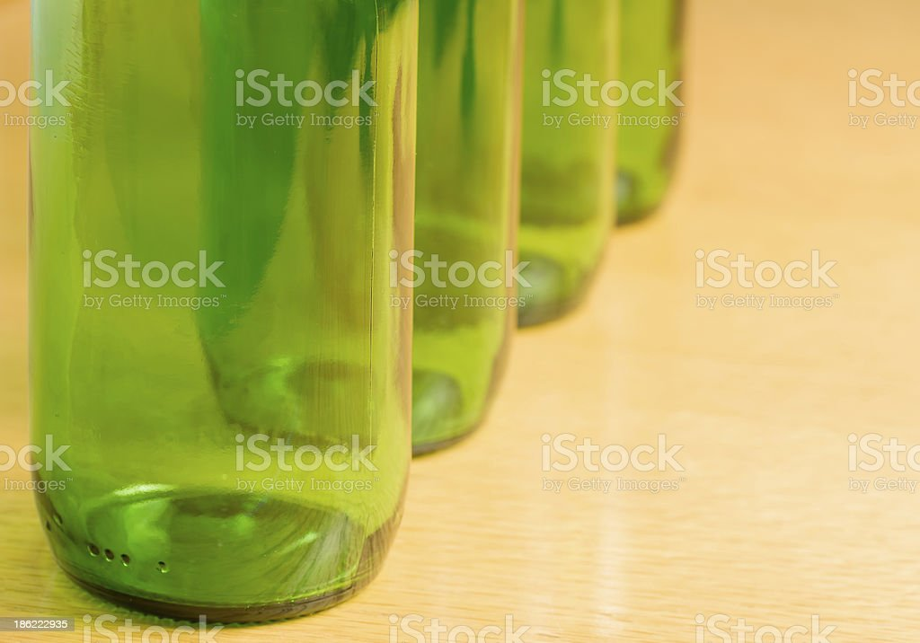 Four green bottles in a row stock photo