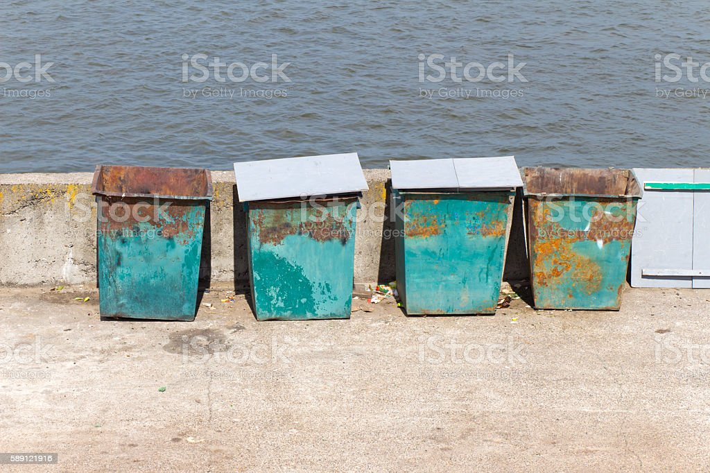 Four (4) green garbage containers standing on the stone embankme stock photo