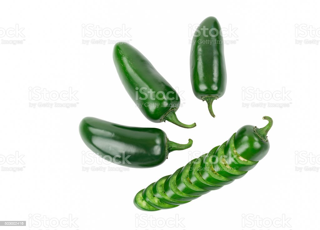 Four Green Jalapeno Peppers One Pepper is Sliced stock photo