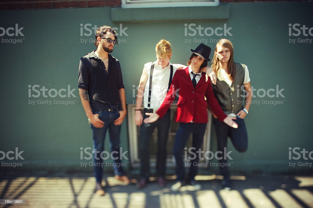 Four Guys Standing Against a Wall royalty-free stock photo