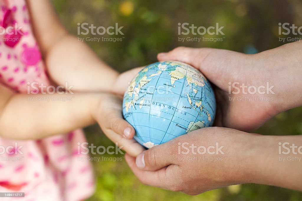 Four hands, holding the globe stock photo