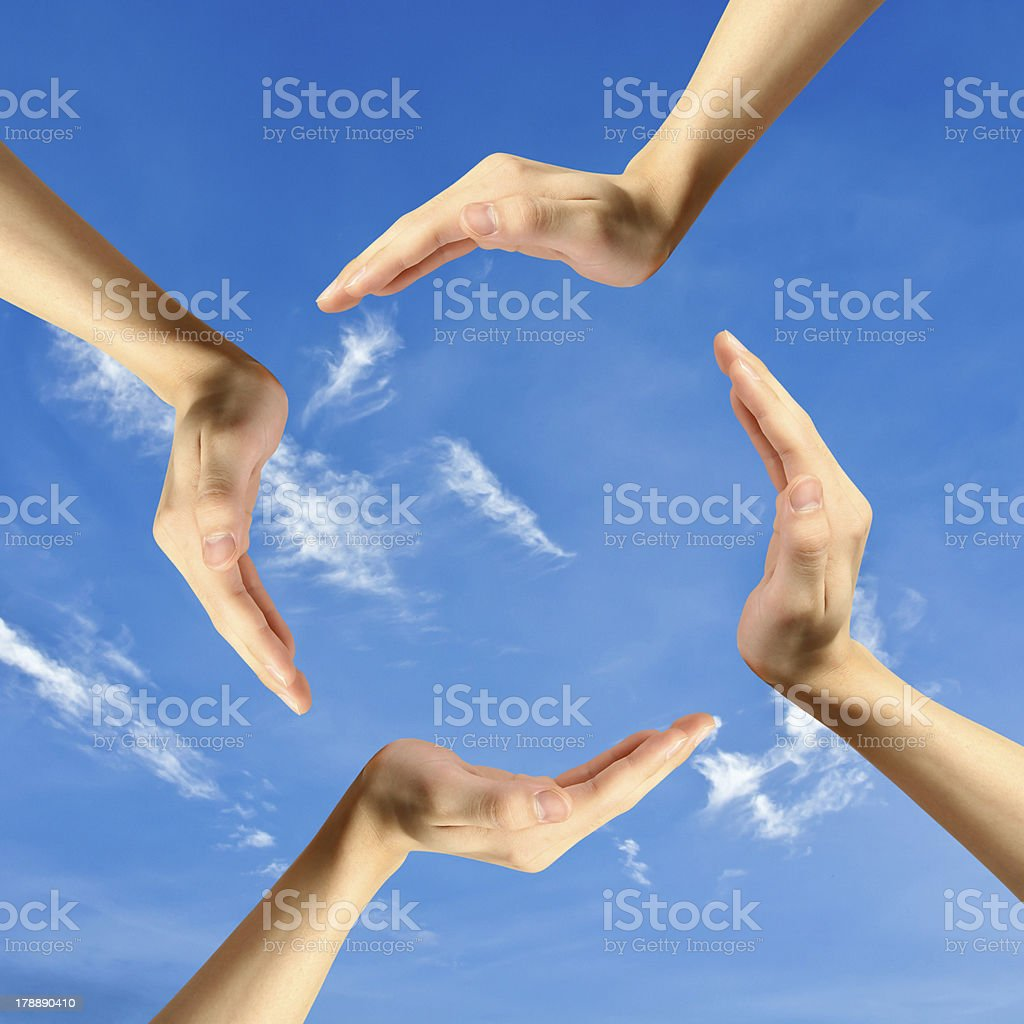 Four hands isolated on sky backgrounds stock photo