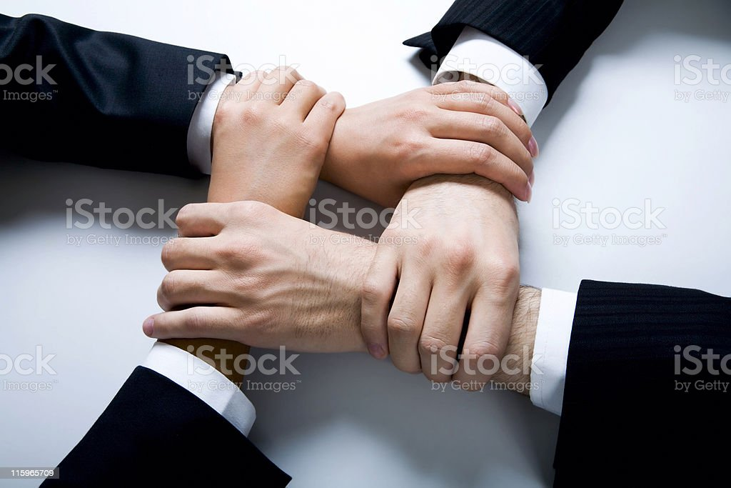 Four hands joined together in harmony royalty-free stock photo