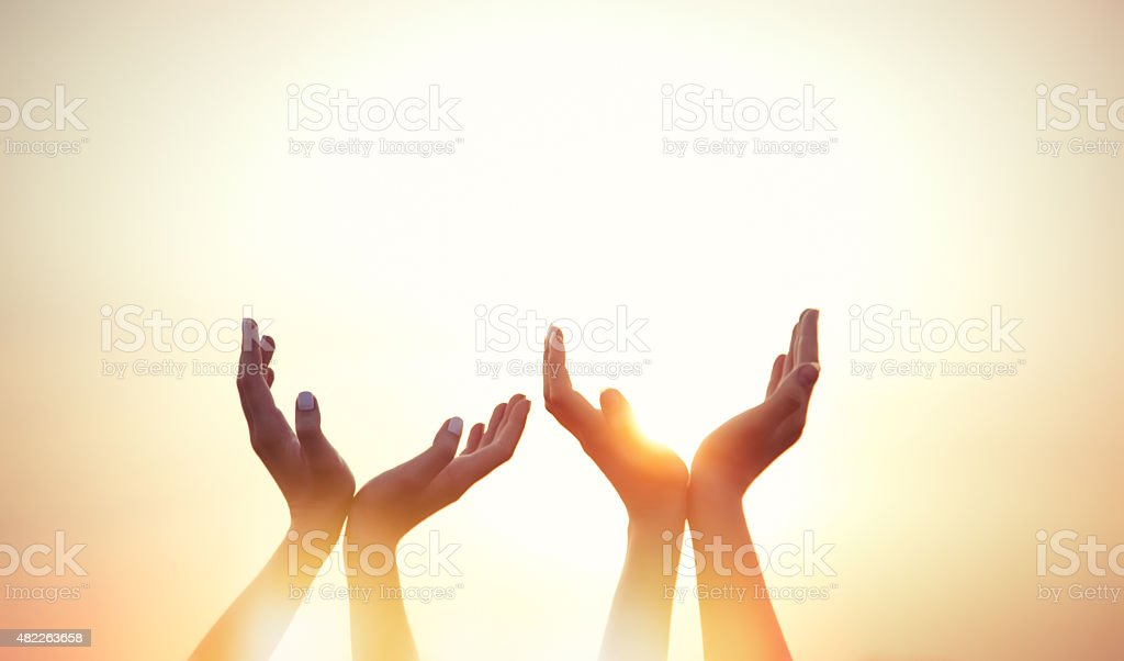 four hands on sunset stock photo