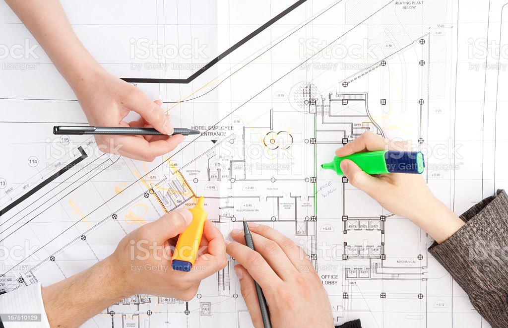 Four hands working on architectural blueprints royalty-free stock photo