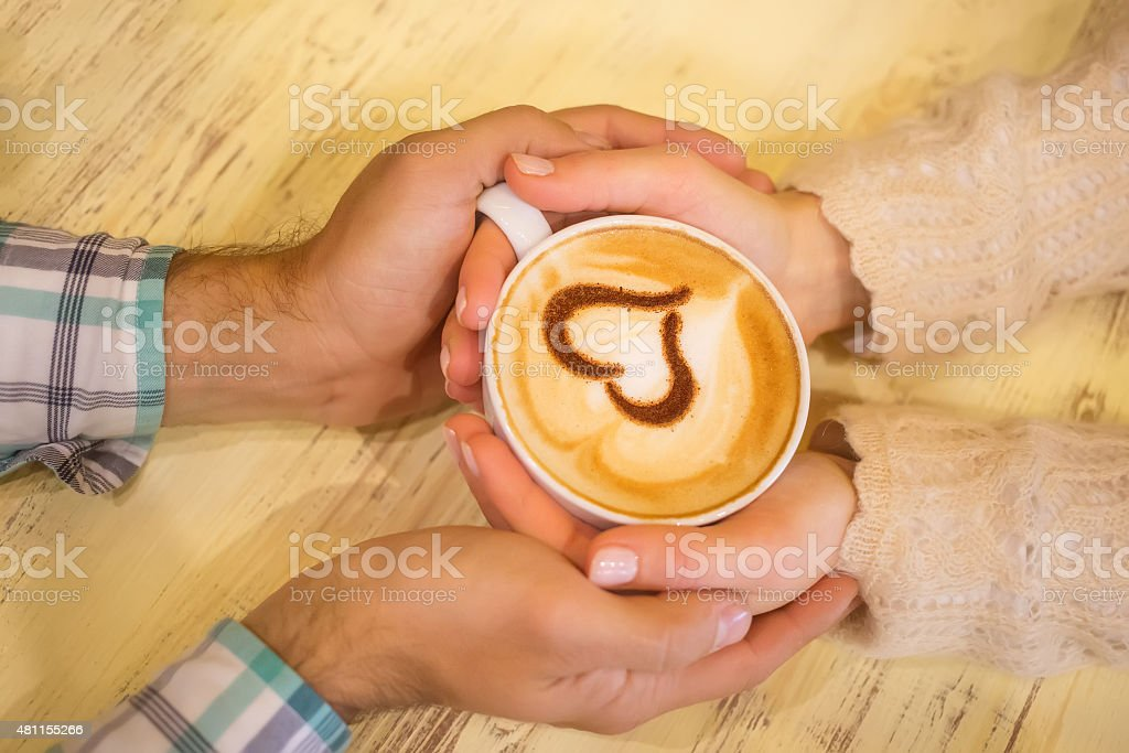 Four hands wrapped around a cup of coffee stock photo