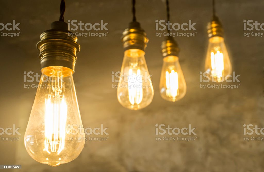 Four hanging light bulbs over oxide dark color concrete background stock photo