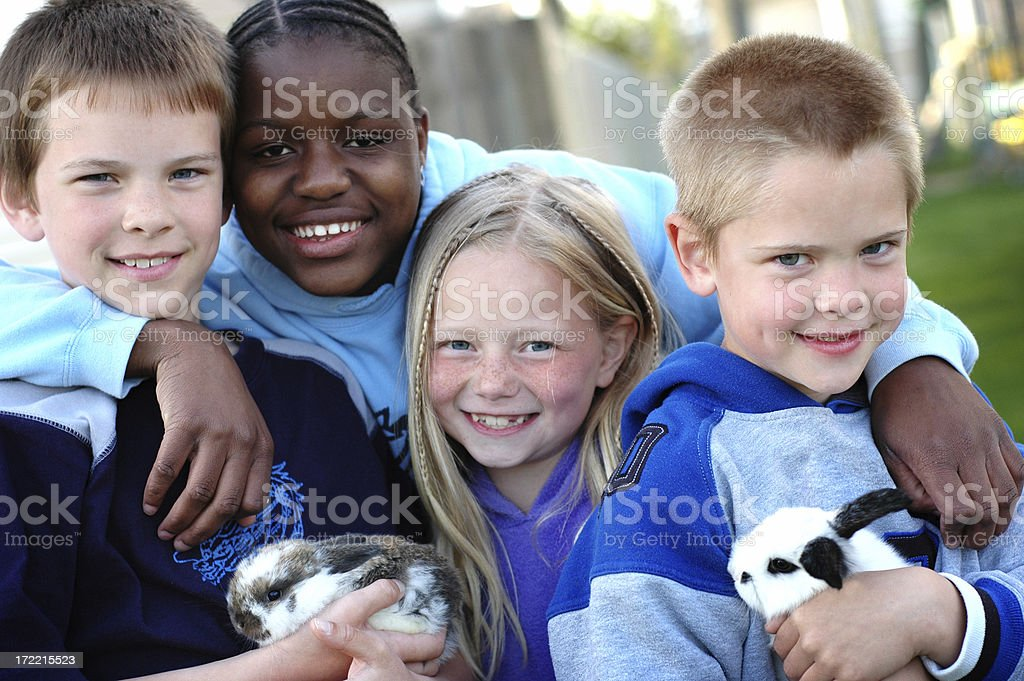 Four Happy Children and Two Bunnies royalty-free stock photo