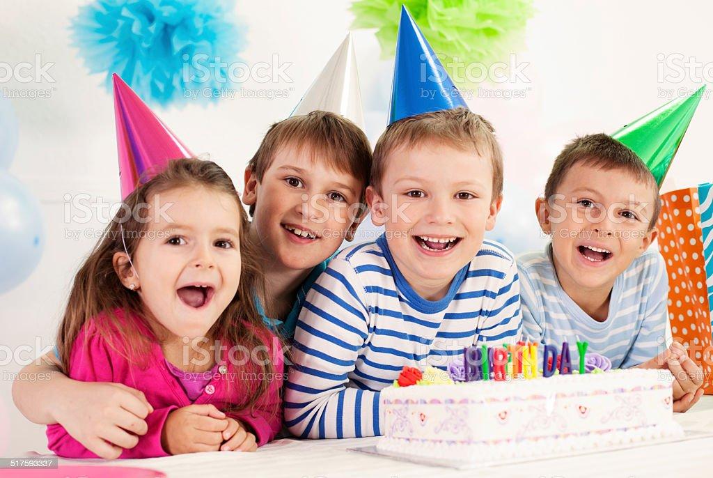 Four happy children celebrating a birthday stock photo