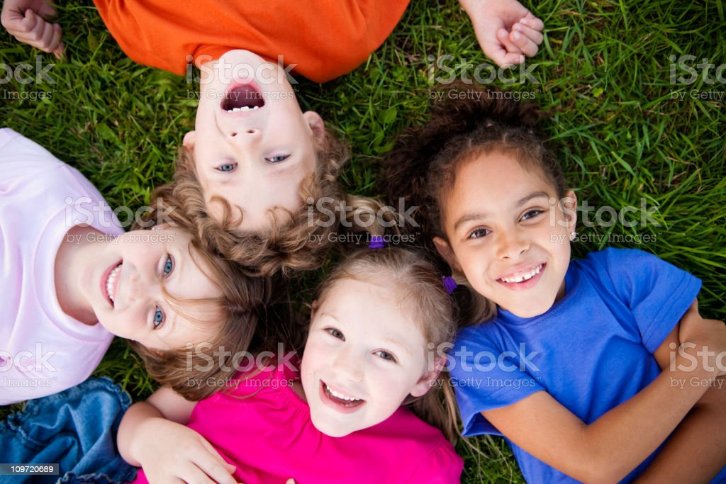Four Happy Children Laughing and Smiling in the Grass royalty-free stock photo