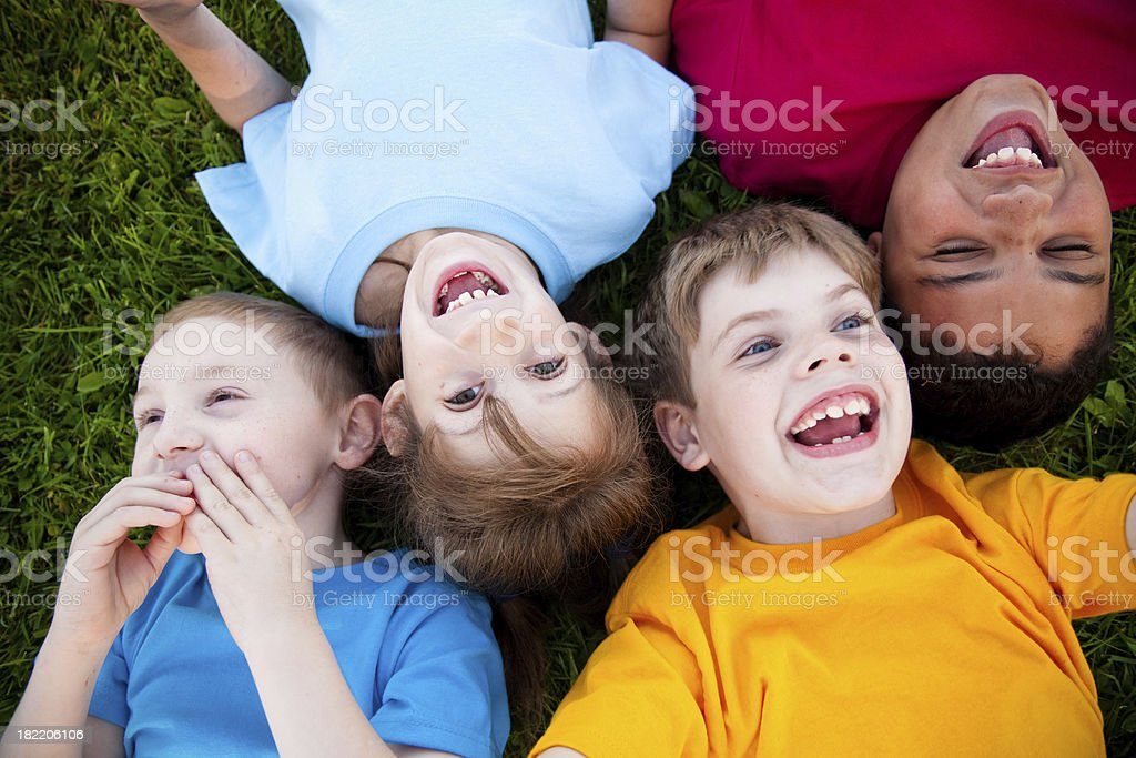 Four Happy Children Laughing in the Grass royalty-free stock photo