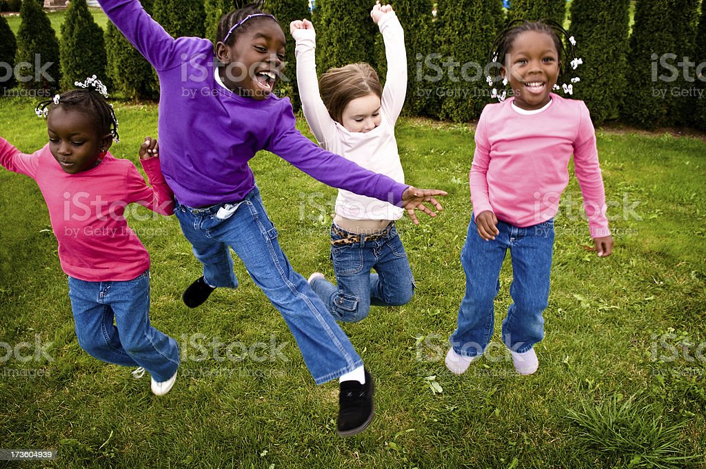 Four Happy Girls Jumping Outside royalty-free stock photo