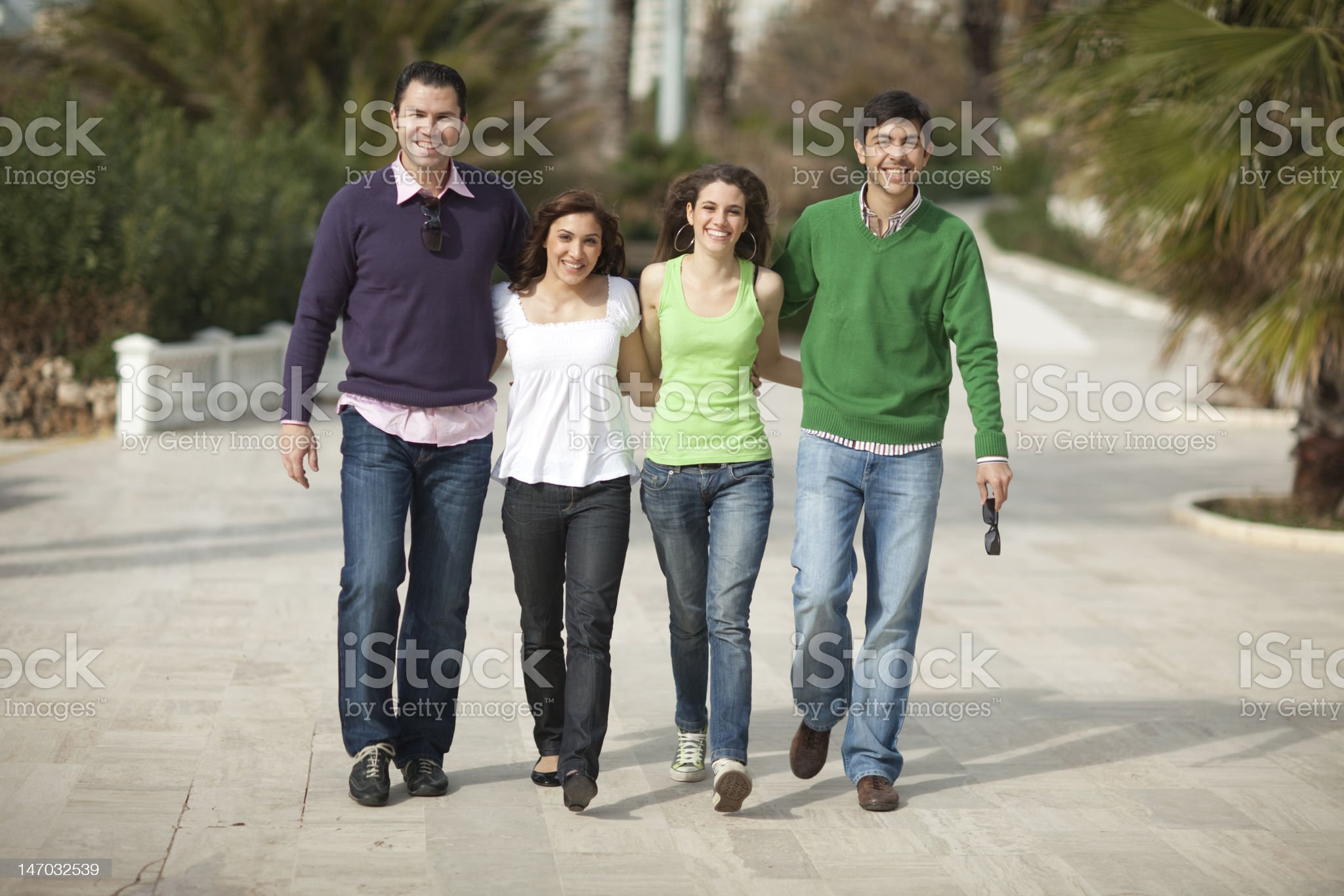 Four happy people walking royalty-free stock photo