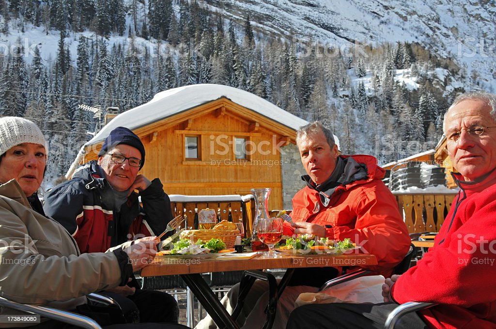 Four happy senior skiers having lunch outdoors stock photo