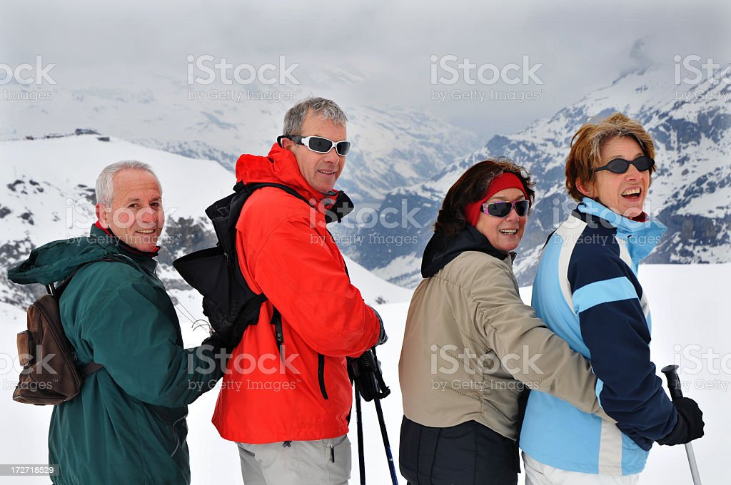 Four Happy Seniors Looking At Camera On Ski Slope royalty-free stock photo