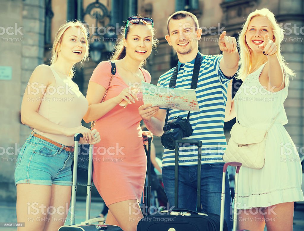 Four happy traveling people using paper map stock photo