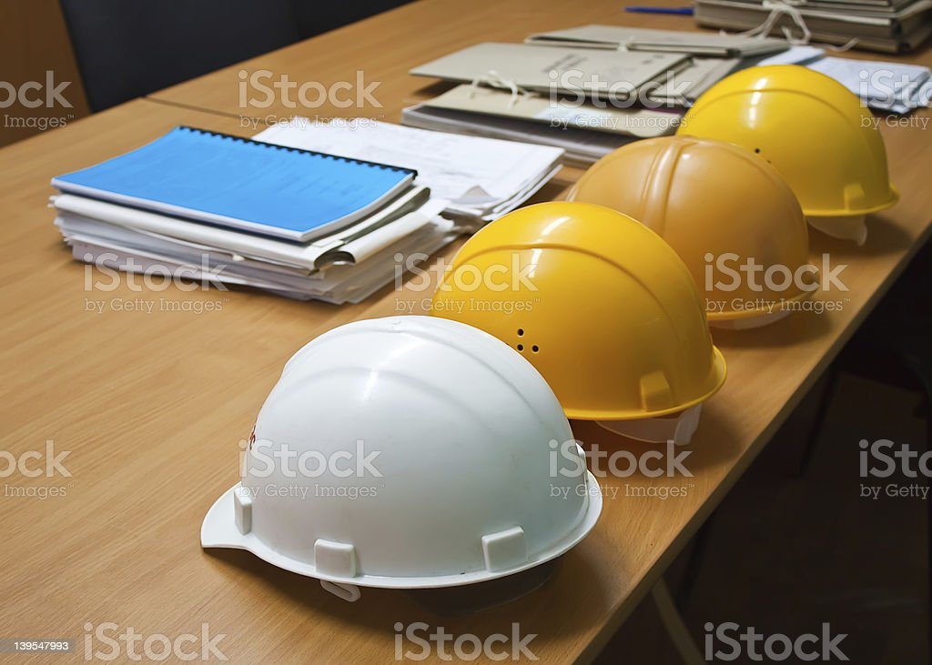 Four hard hats on a wooden desk next to documents stock photo