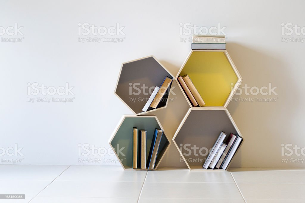 Four hexagon shaped decorative shelves storing and displaying books stock photo