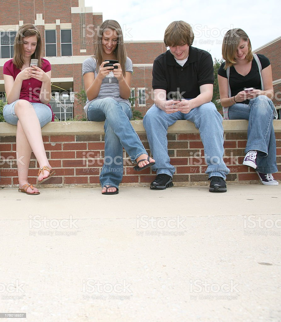 Four High School Friends Having Fun Texting on Cell Phones royalty-free stock photo