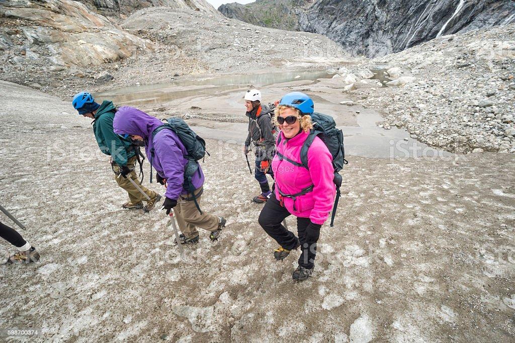 Four hikers begin trekking up Lemon Glacier stock photo