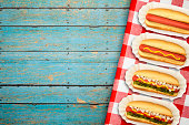 Four Hotdogs Plain to Dressed on Rustic Blue Picnic Table