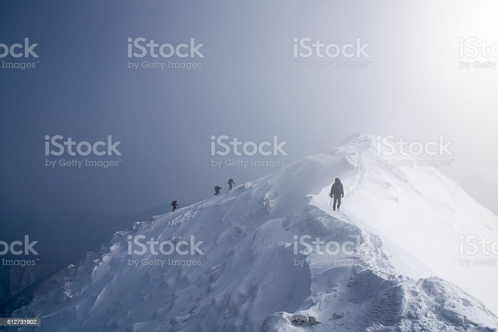 Four ice climbers scaling a mountains summit stock photo