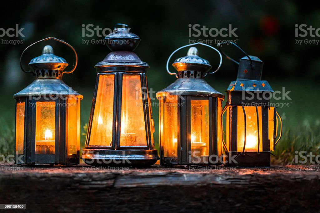 Four illuminated lanterns in a row outdoors in garden stock photo