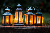 Four illuminated lanterns in a row outdoors in garden