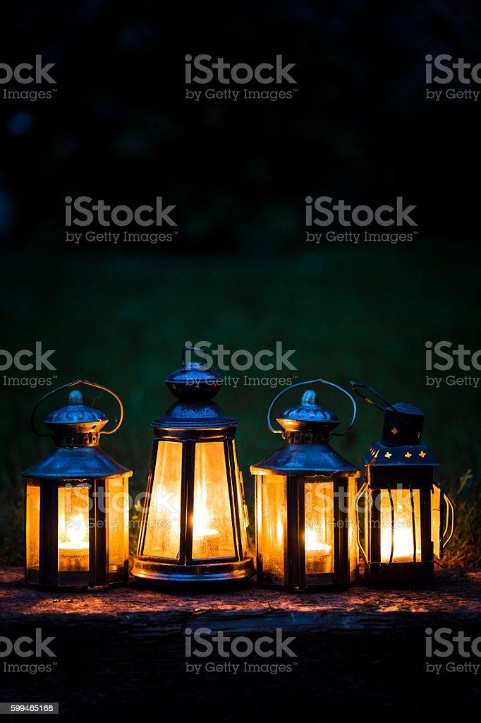 Four illuminated lanterns in a row outdoors in garden stock photo
