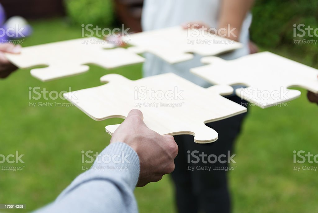 Four individuals unite with giant puzzle pieces royalty-free stock photo