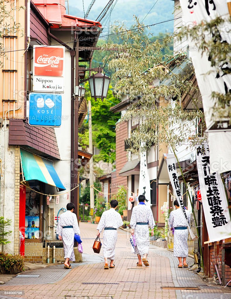Four Japanese men wearing yukatas walking in Shibu-Onsen street stock photo
