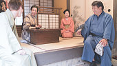 Four Japanese people in Kimono chatting in a room