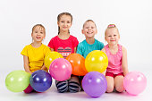 Four joyful child with balloons on a white background