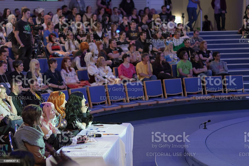 Four jurors sitting at the table during cosplay contest stock photo