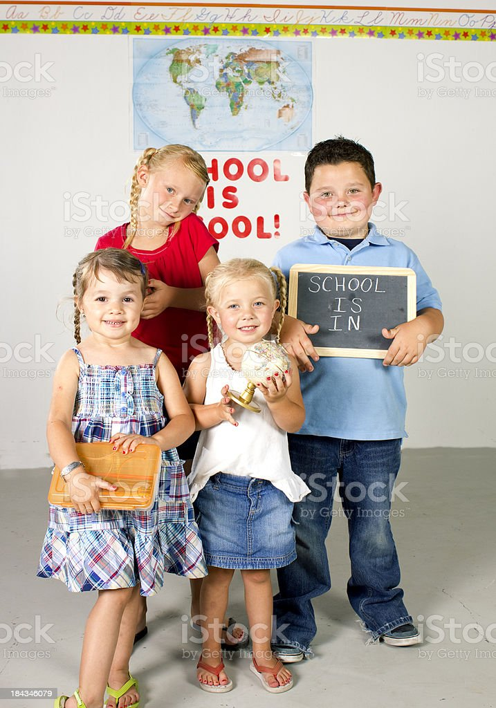 Four kids in class room with school supelies stock photo