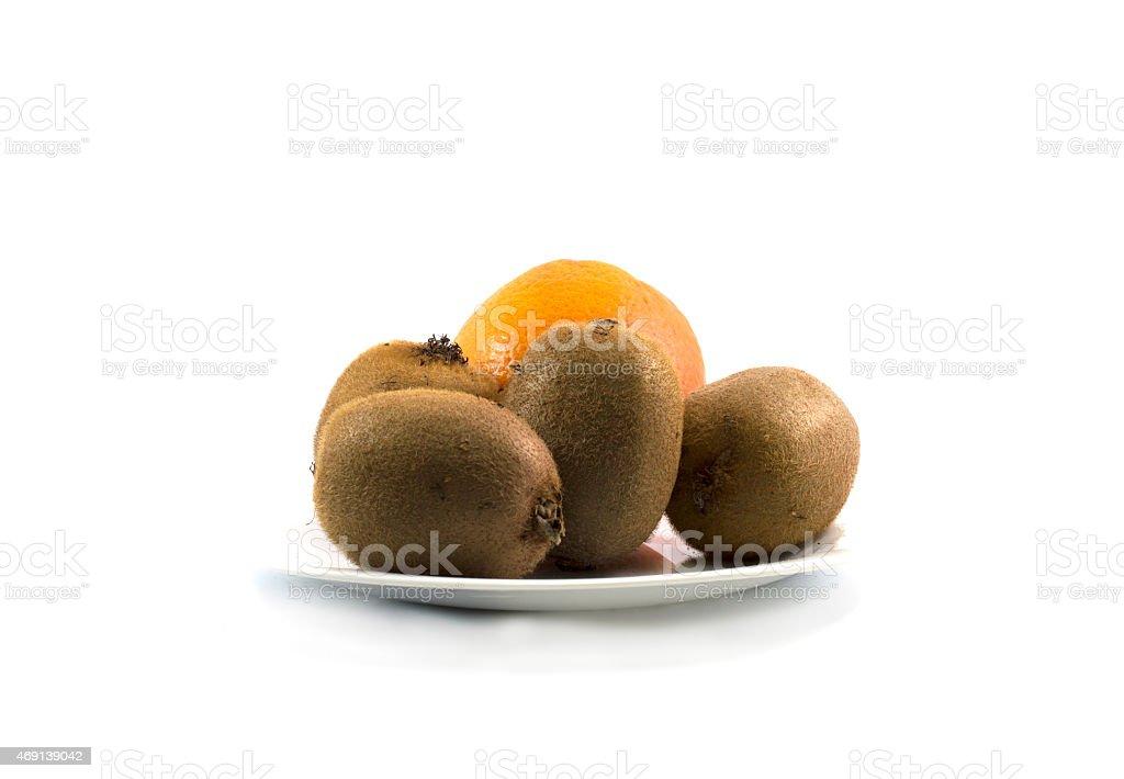 four kiwis and orange, on a white plate stock photo