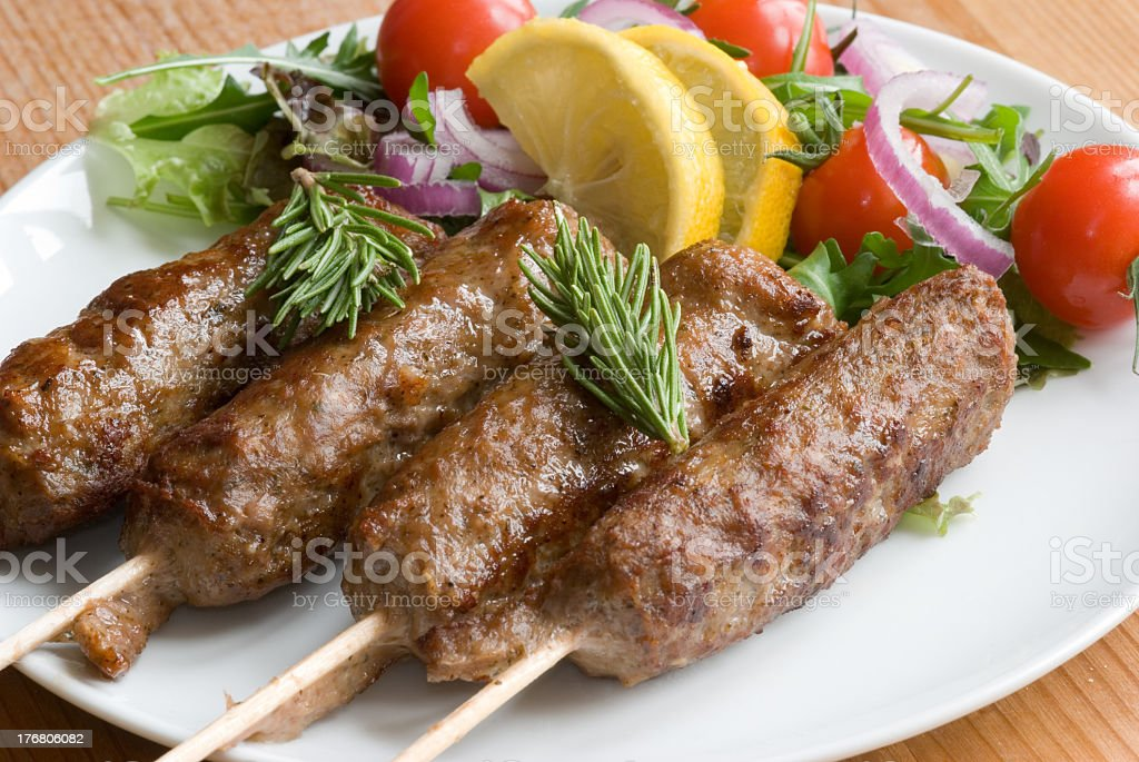 Four lamb kebabs served with a side salad and lemon wedges royalty-free stock photo