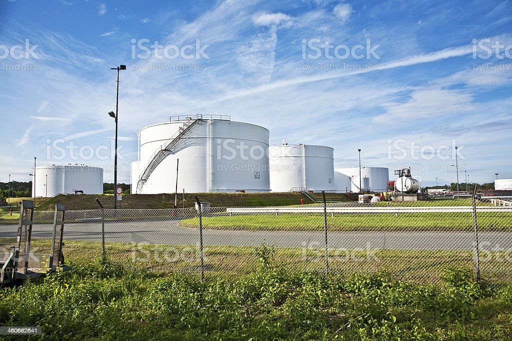 Four large white tanks at a tank farm with a blue sky stock photo