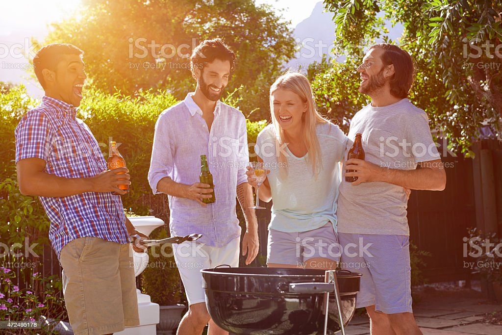 Four laughing people gathered around BBQ at a garden party stock photo