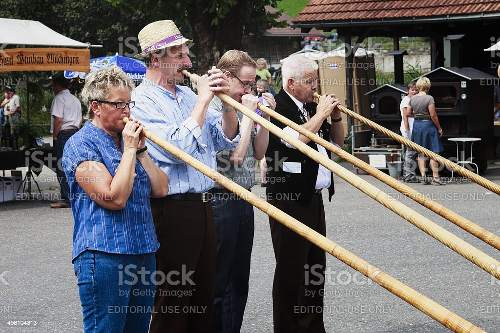 Four local people entertain with alphorns at Farmer's Market stock photo