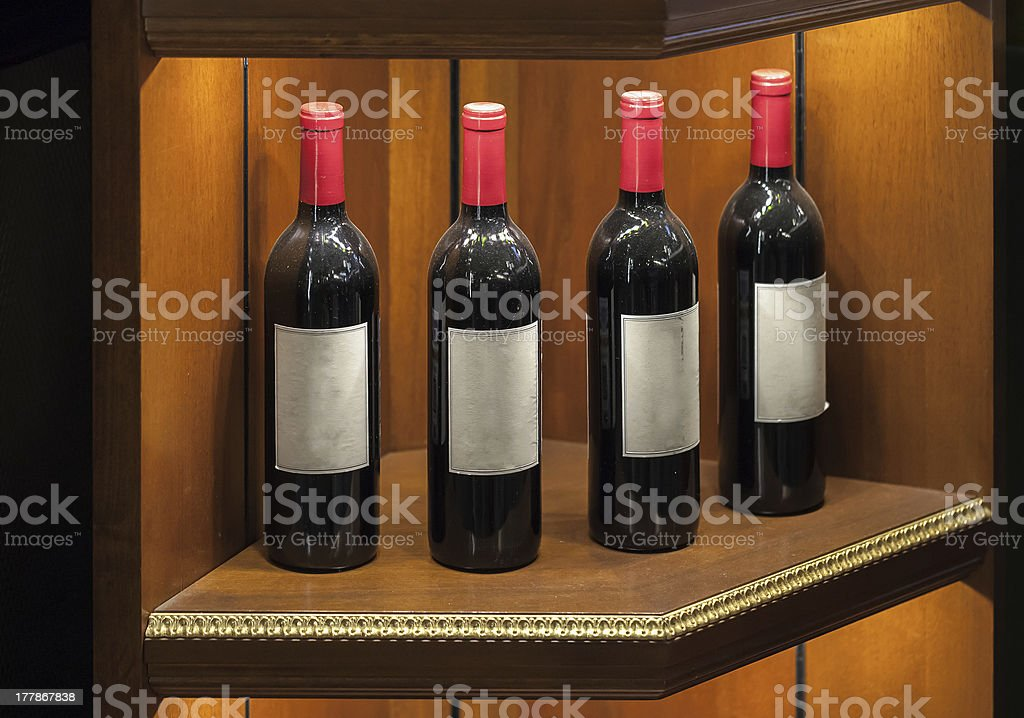 Four luxury red vine bottles on wooden shelf royalty-free stock photo
