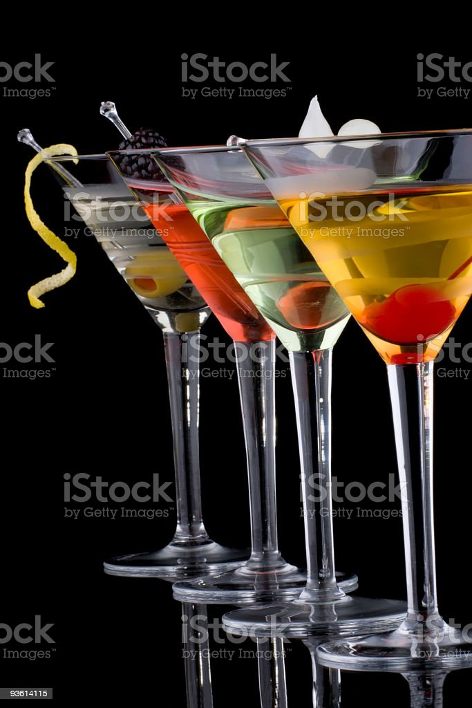Four martinis with different garnishes, lined in a row stock photo