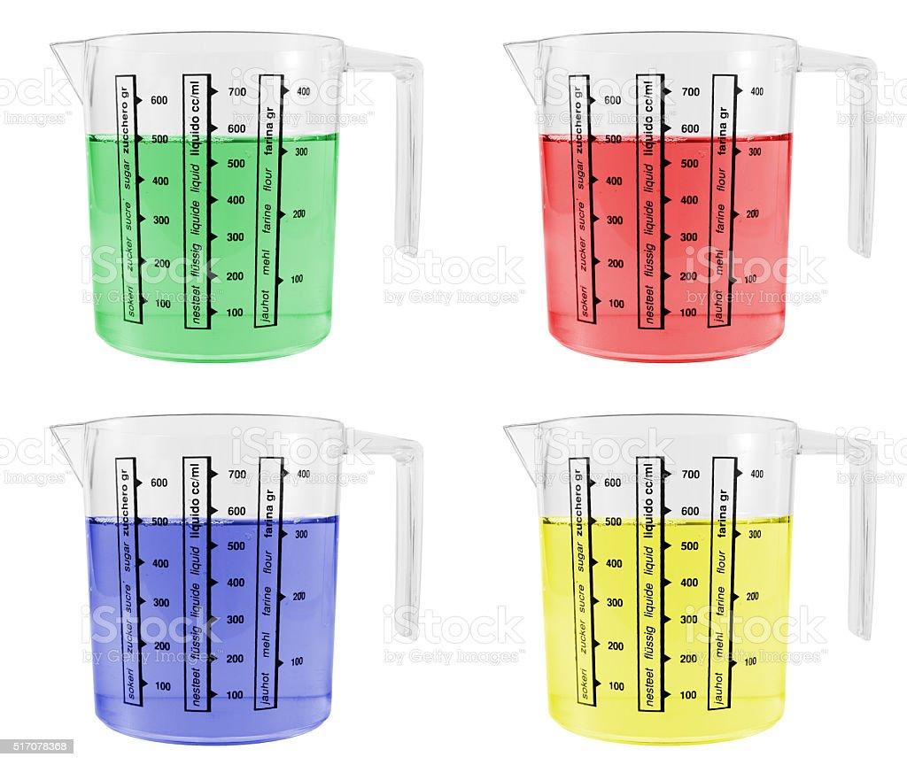 Four Measuring Jugs Full of Coloured Liquids stock photo
