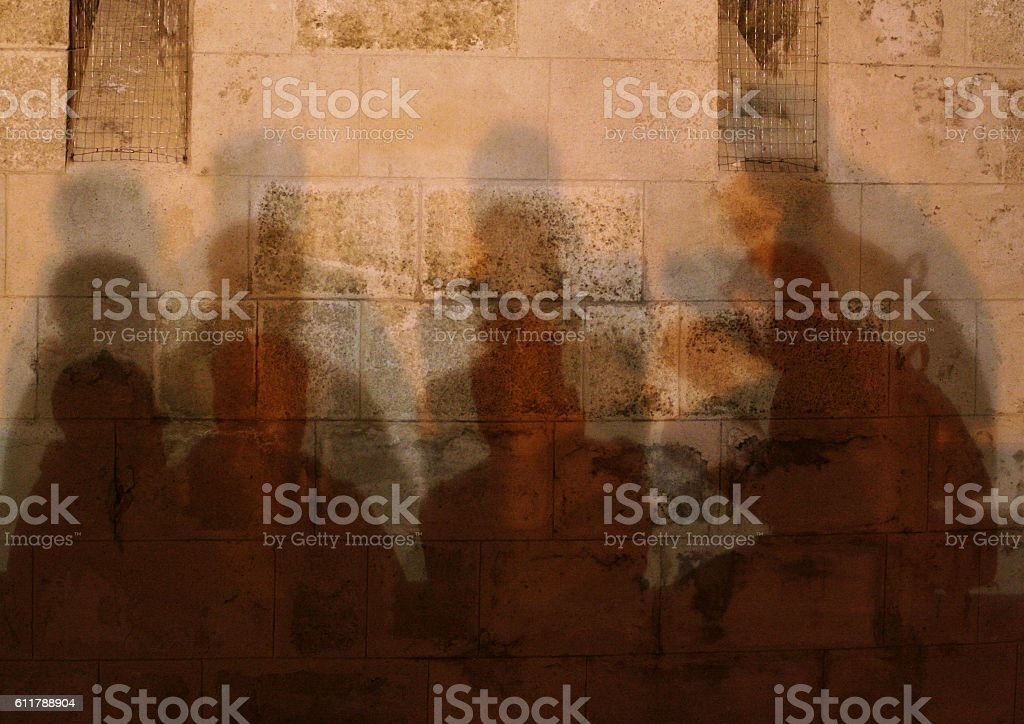 Four men conversing in the shade stock photo