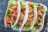 Four mexican tacos on a black background