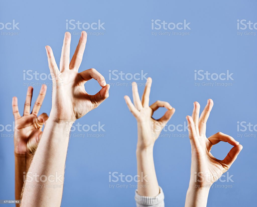 Four mixed hands signalling OK with gestures against sky blue stock photo